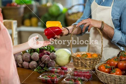 Vendor giving bell pepper to the woman at the grocery store
