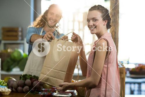 Vendor handing a bag of vegetables to woman at grocery store