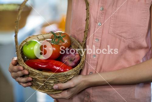 Woman holding a basket with variety of fruits and vegetables