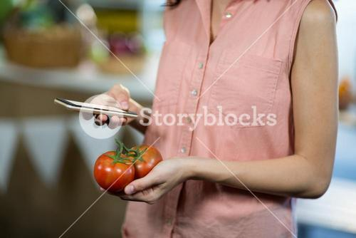 Woman using smartphone while holding tomatoes