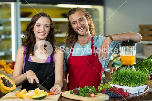 Two shop assistant chopping fruits at the counter in health grocery shop