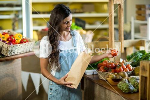 Woman putting fresh tomatoes in the vegetable bag