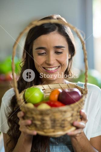 Smiling woman holding a basket of fruits