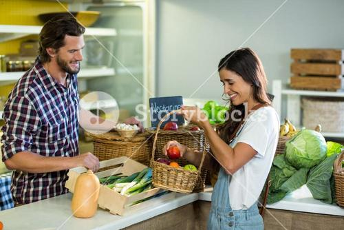 Smiling woman with vendor at the counter at grocery store