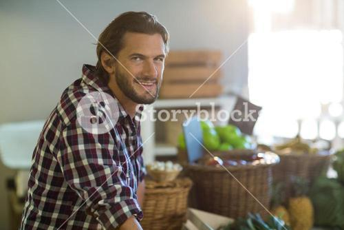 Smiling vendor standing at the counter in the grocery store