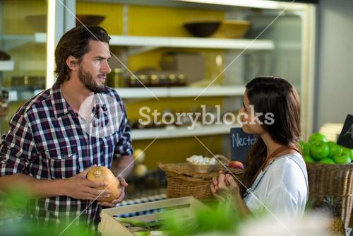 Woman interacting with vendor while buying vegetables