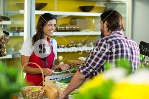 Woman vendor interacting with the man in the grocery store