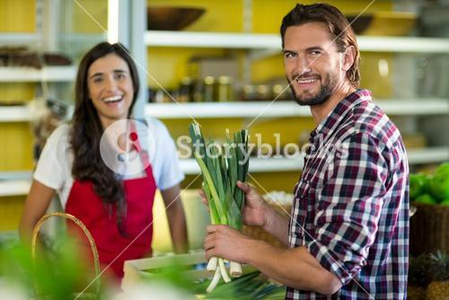 Smiling man holding a bunch of spring onions in the grocery store