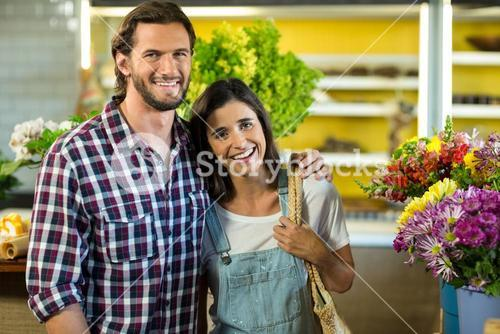 Happy couple standing in the florist shop
