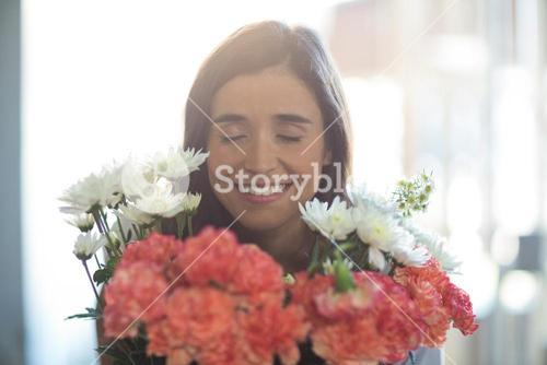 Smiling woman holding a bouquet with eyes closed