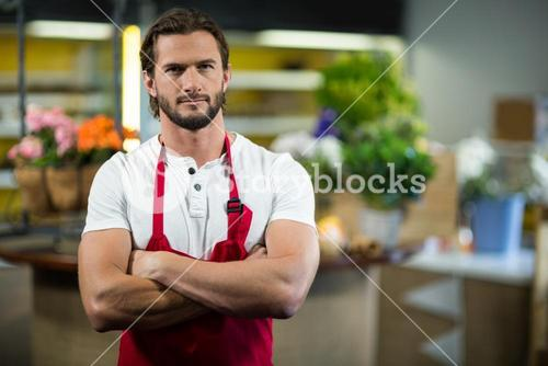 Florist standing in florist shop with arms crossed
