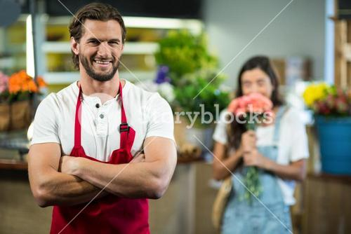 Smiling florist standing in florist shop with arms crossed