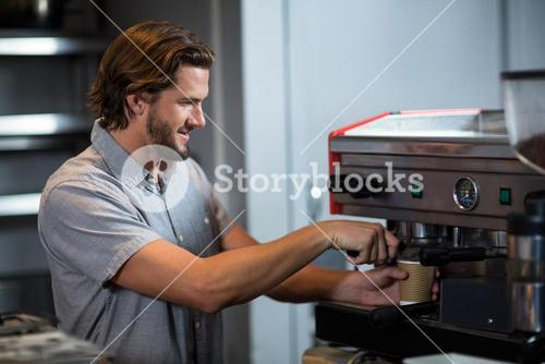 Male staff making cup of coffee at counter
