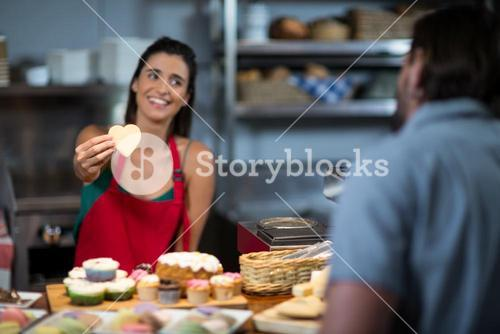 Smiling female staff giving heart shape cookie to customer at counter