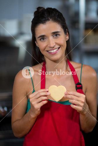 Portrait of smiling female staff showing heart shape cookie at counter