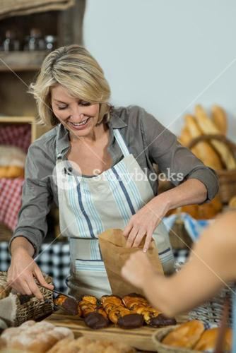 Saleswoman packing parcel for customer at counter