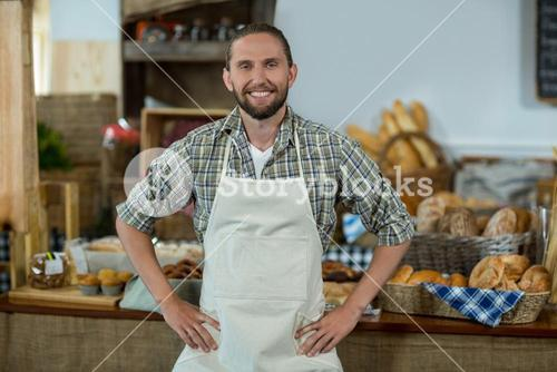 Portrait of smiling male staff standing with hands on hip