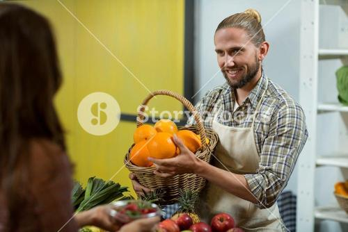 Smiling vendor offering oranges to the woman at the counter