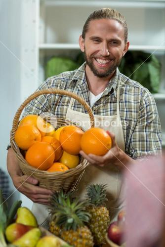 Smiling vendor offering oranges at the counter