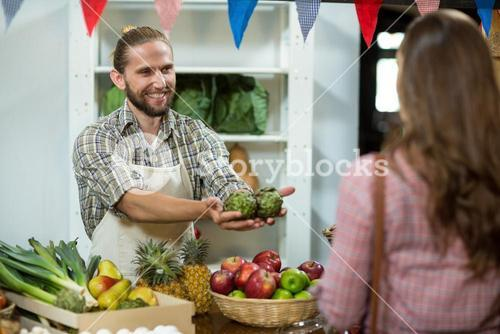 Smiling vendor offering custard apples to the woman at the counter