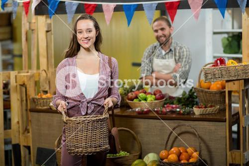 Smiling woman holding a basket at the counter in the grocery store