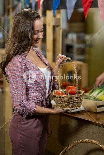 Smiling woman holding a basket of tomatoes