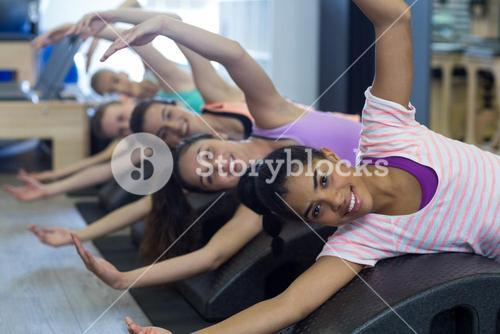 Smiling fit women exercising on arc barrel