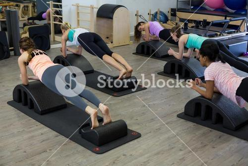 Fit women exercising on arc barrel