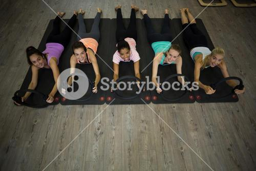 Group of fit women exercising with pilates ring