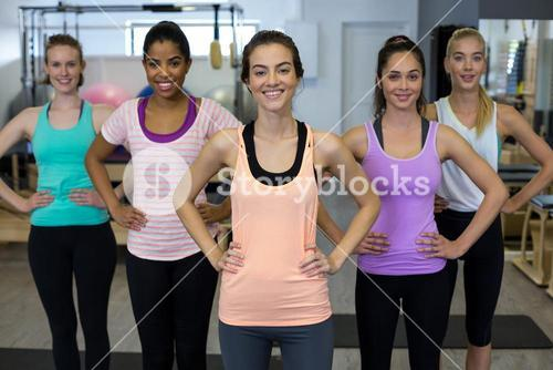 Group of smiling women standing with hands on hip
