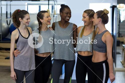 Group of smiling women standing together with arms around