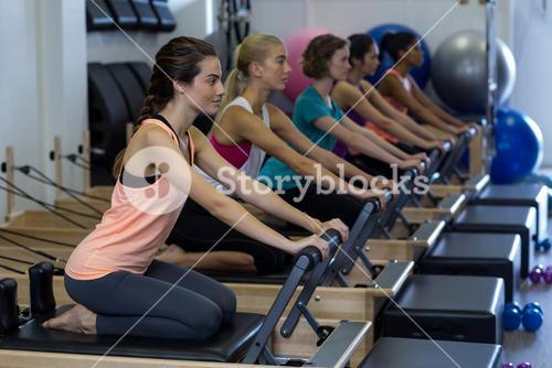 Determined women practicing stretching exercise on reformer