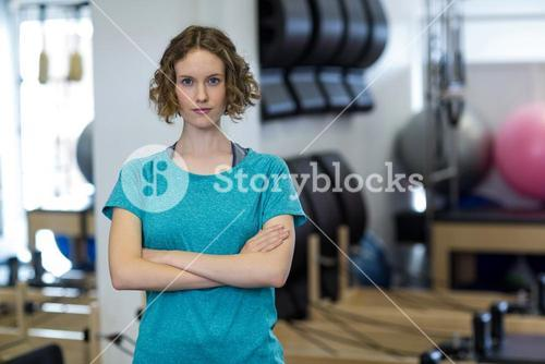 Portrait of fit woman standing with arms crossed