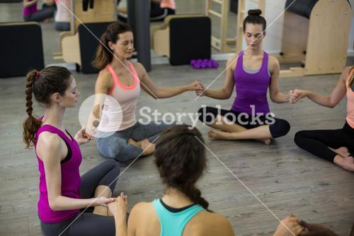 Group of women holding hands and meditating