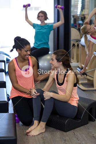 Female trainer assisting woman with stretching exercise on arc barrel