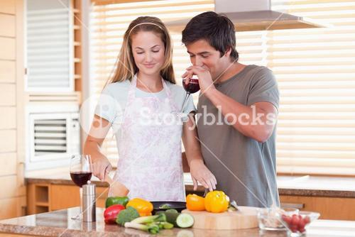 Young couple cooking dinner while drinking red wine