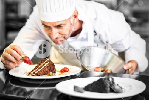 Concentrated male pastry chef decorating desserts