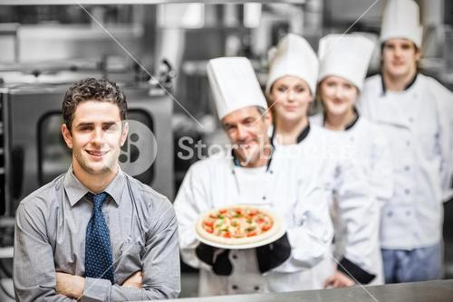 Manager standing in front of chefs holding pizza in kitchen