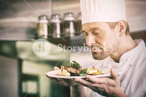 Male chef with eyes closed smelling gourmet food