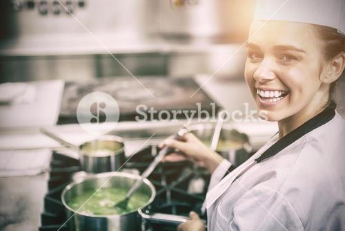 Portrait of young cheerful chef stirring sauce
