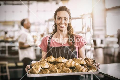 Female baker showing tray of fresh croissants