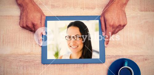 Composite image of hand holding on digital tablet over table by coffee