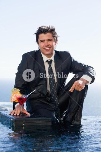 Portrait of a businessman posing with a cocktail in a briefcase