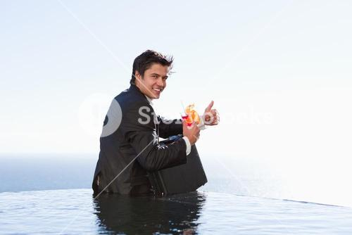 Portrait of a businessman posing with a cocktail and a briefcase