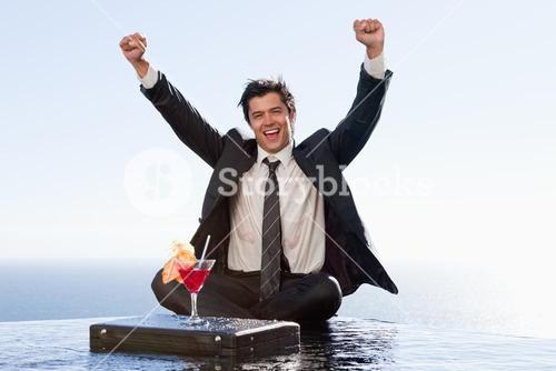 Businessman relaxing with a cocktail and his fists up