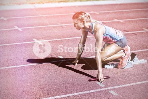 Female athlete ready to start relay race