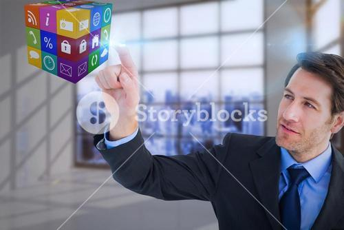 Composite image of serious businessman pointing at cube