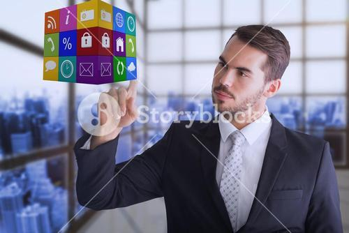 Composite image of thoughtful businessman pointing cube with his finger