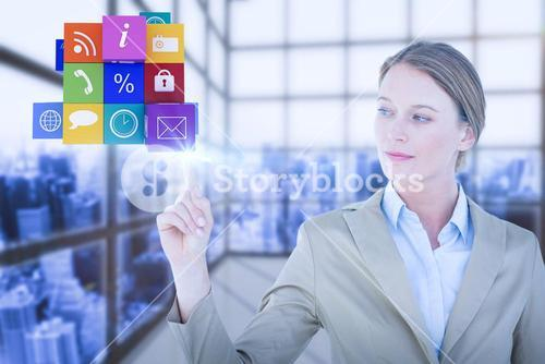 Composite image of businesswoman pointing cube with her finger