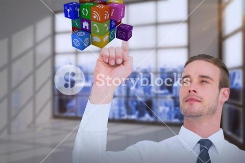 Composite image of cheerful businessman pointing cube with his finger